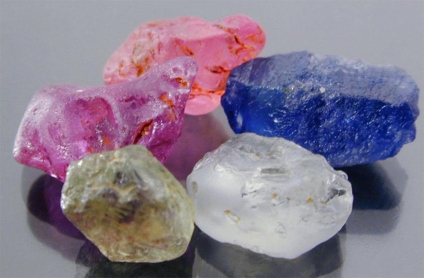 Необработанные сапфиры - фиолетовый и розовый из Мадагаскара, синий из Кашмира, шартрез и белый из Монтаны, США.
