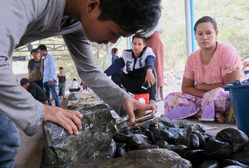 Обследование нефритовых горных пород с помощью портативного ультрафиолетового светодиодного фонаря в нефритовом рынке Мандалай , Мьянма
