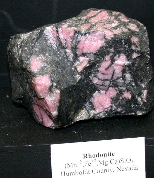 Розовый родонит, контрастирующий с черными оксидами марганца, иногда используется в качестве материала драгоценных камней, как видно на этом образце из округа Гумбольдт, штат Невада